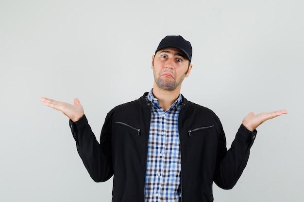 Молодой человек показывает беспомощный жест в рубашке, куртке, кепке и выглядит смущенным, вид спереди.