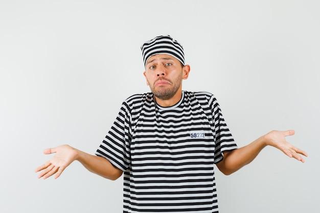 Молодой человек показывает беспомощный жест в полосатой футболке, шляпе и выглядит смущенным.