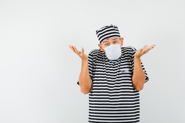 Молодой человек показывает беспомощный жест в полосатой футболке, шляпе, маске и выглядит смущенным.