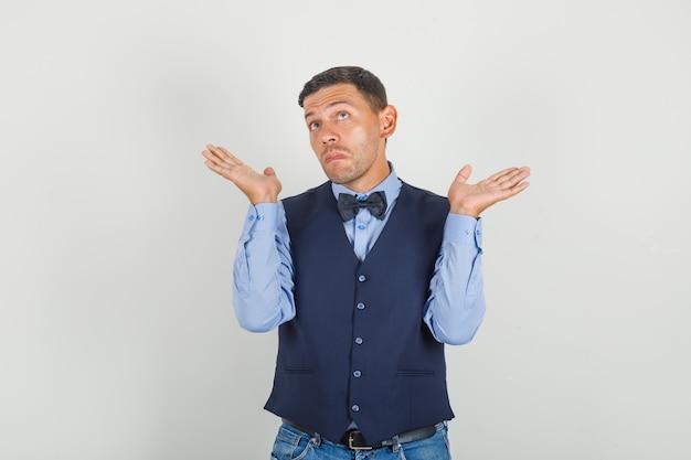 Молодой человек демонстрирует беспомощный жест в костюме, джинсах и выглядит неуверенно.