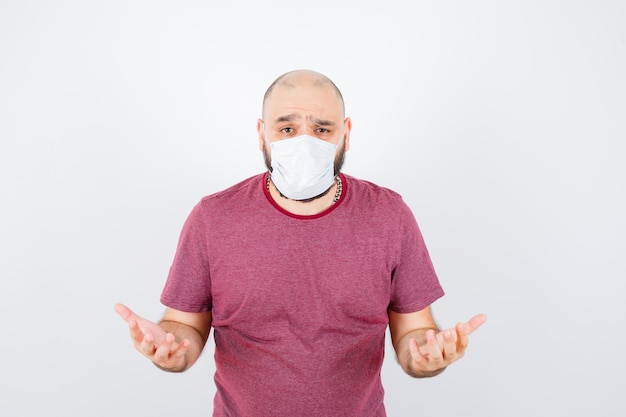 Young man showing helpless gesture in pink t-shirt,mask front view.