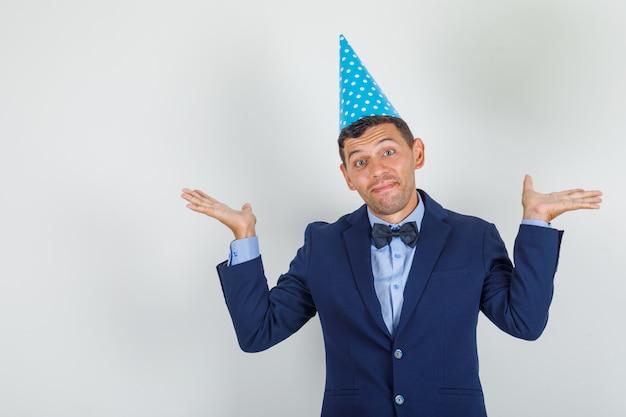 Giovane che mostra gesto impotente in vestito, cappello blu del partito e che sembra confuso
