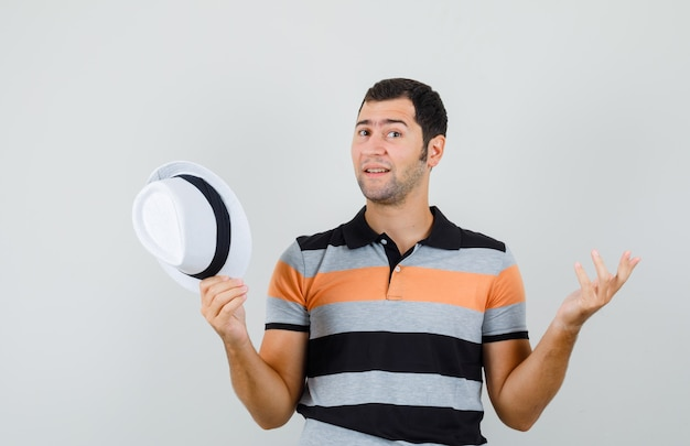 Tシャツ、帽子で帽子を保持し、困惑しているように見えながら無力なジェスチャーを示す若い男。正面図。