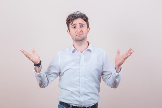 Giovane che mostra gesto impotente in camicia bianca, jeans e sembra confuso