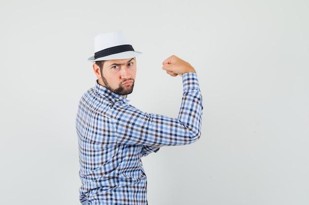 체크 셔츠, 모자 및 단호한 찾고 그의 팔 근육을 보여주는 젊은 남자.