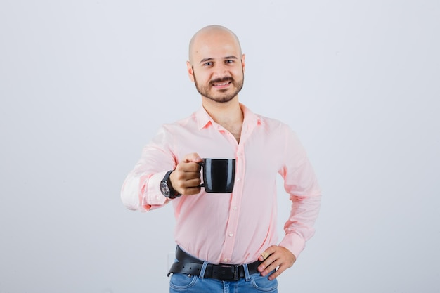 Young man showing his cup full of tea in pink shirt,jeans and looking satisfied. front view.