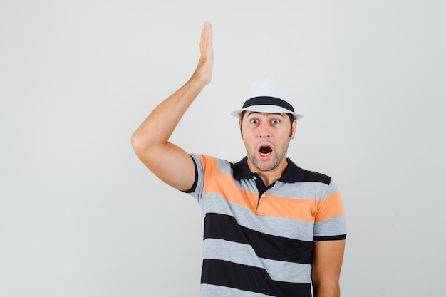 Young man showing his feelings in t-shirt,hat and looking surprised. front view.