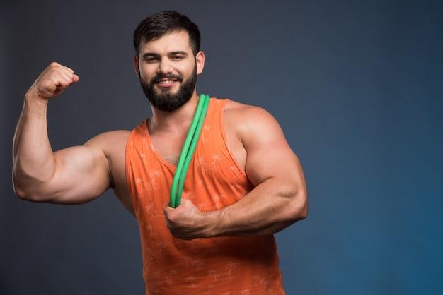 Молодой человек показывает свои мышцы и держит резину для спорта.