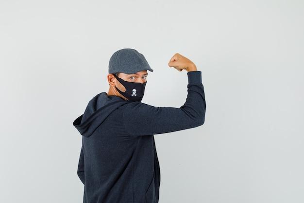 T- 셔츠, 재킷, 모자, 마스크에 그의 근육을 표시 하 고 자신감을 찾고 젊은 남자. .