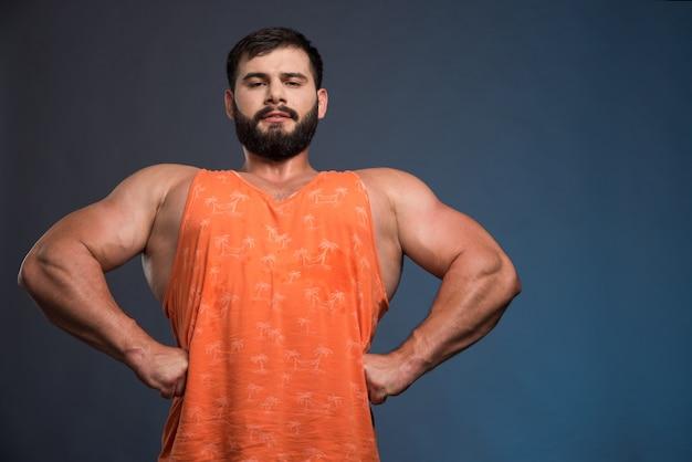 Молодой человек показывает свои мышцы на синей стене.