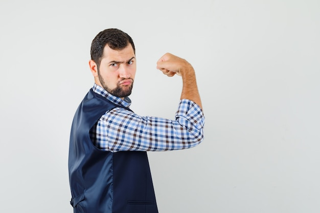 Young man showing his muscles in shirt, vest and looking powerful .