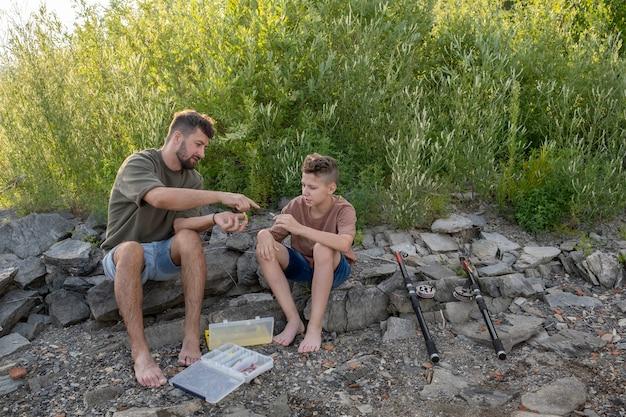 십대 아들에게 낚시 미끼를 준비하는 방법을 보여주는 젊은 남자