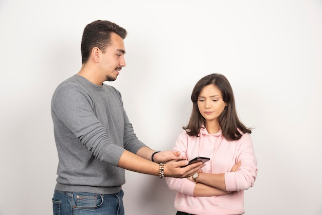 Young man showing his telephone to woman.