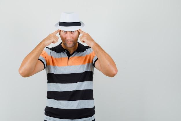縞模様のtシャツ、帽子、真剣に見える、正面図で彼の寺院を示す若い男。テキスト用のスペース