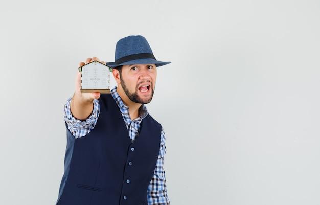 셔츠, 조끼, 모자에 집 모델을 보여주는 젊은 남자