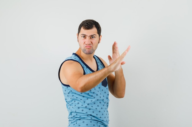 Young man showing karate chop gesture in blue singlet and looking confident. front view.