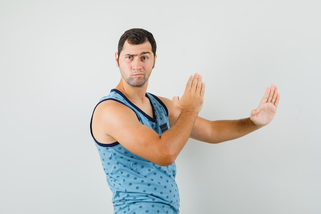 Young man showing karate chop gesture in blue singlet and looking strict. front view.