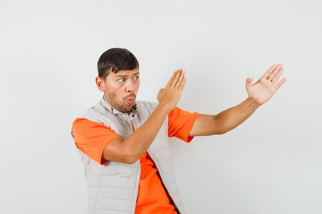 Giovane che mostra il gesto di taglio di karate in maglietta, giacca e sembra potente