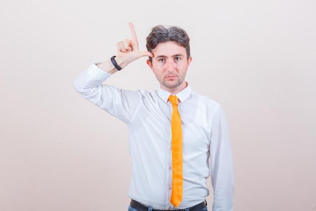 젊은 남자 셔츠, 청바지에 패자 기호를 보여주는 화가 찾고