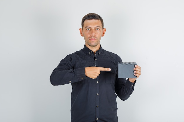 Young man showing mini notebook in black shirt, front view.