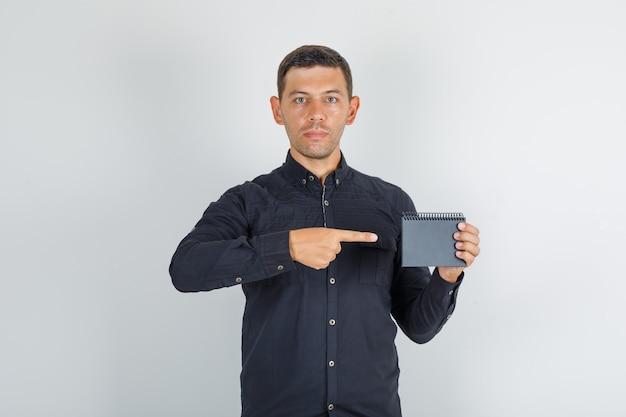 Молодой человек показывает мини-ноутбук в черной рубашке, вид спереди.