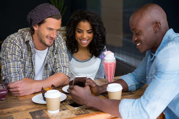 Young man showing mobile phone to friends at table in coffee shop