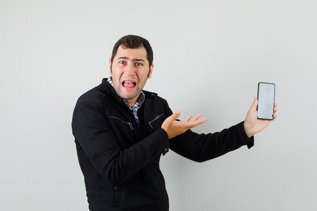 Молодой человек показывает мобильный телефон в рубашке, куртке и выглядит озадаченным, вид спереди.