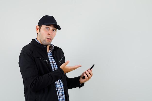Молодой человек показывает мобильный телефон в рубашке, куртке, кепке и выглядит озадаченным. передний план.