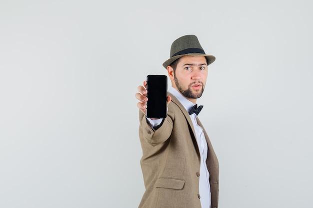 スーツ、帽子、自信を持って、正面図で携帯電話を示す若い男。