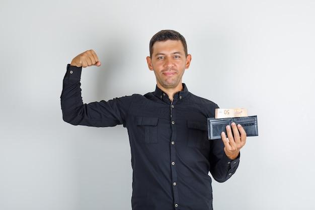 Молодой человек показывает мышцы с кошельком в черной рубашке и выглядит уверенно