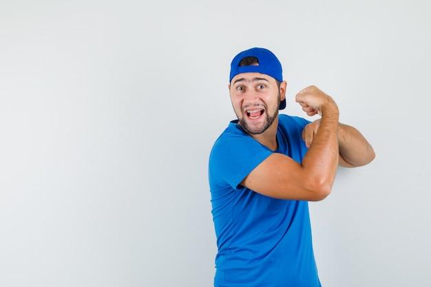 青いtシャツとキャップで腕の筋肉を示し、強力に見える若い男