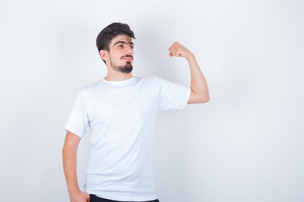 Молодой человек показывает мышцы рук в белой футболке и выглядит уверенно