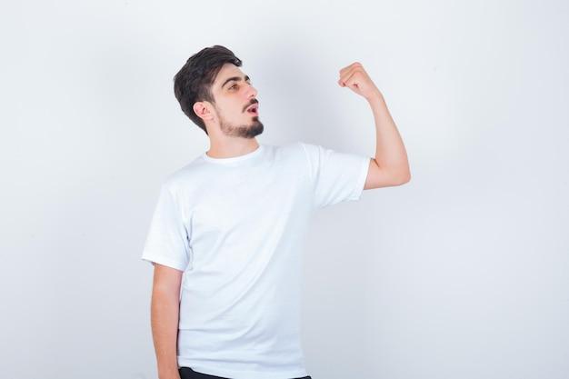 白いtシャツで腕の筋肉を示し、自信を持って見える若い男