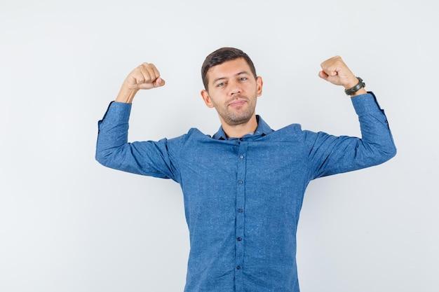 青いシャツを着て腕の筋肉を見せて、力強く見える若い男。正面図。