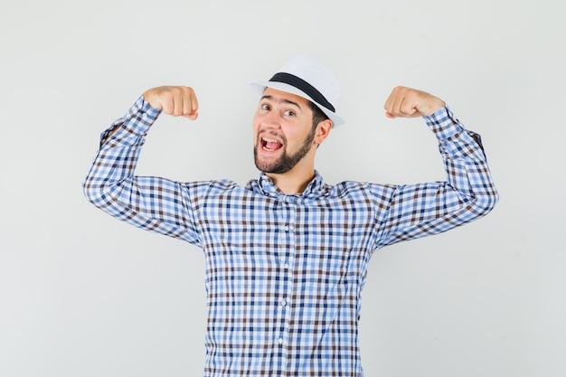 체크 셔츠, 모자에 팔의 근육을 보여주는 젊은 남자가 자랑스럽게 찾고