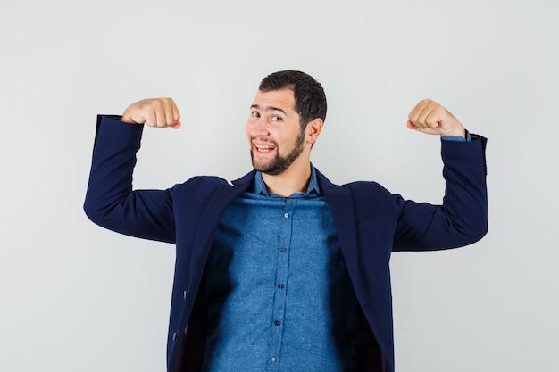 셔츠, 재킷에 팔의 근육을 보여주는 쾌활한 찾고 젊은 남자.