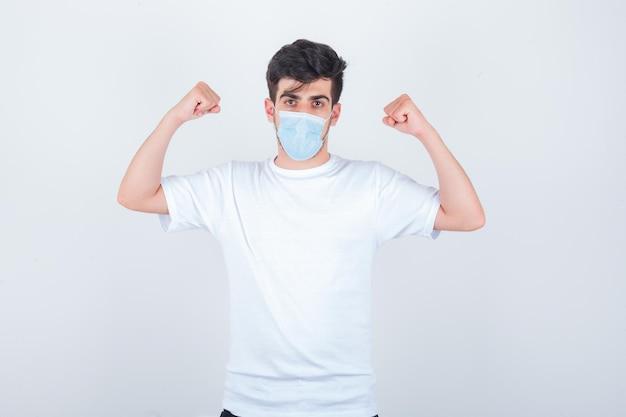Молодой человек показывает мышцы рук в белой футболке, маске и выглядит сильным