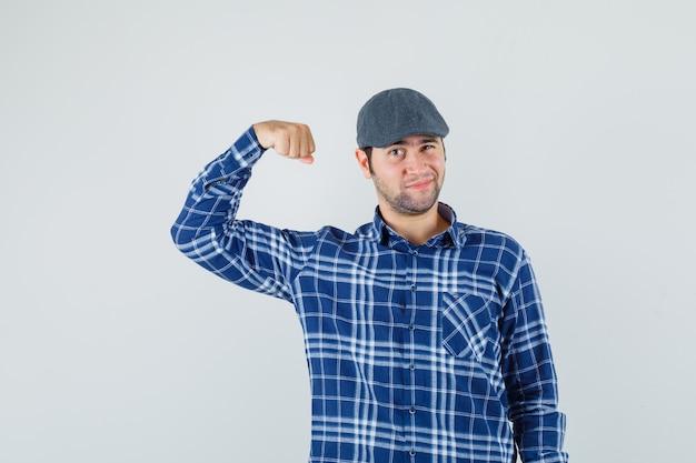 Giovane che mostra i muscoli, occhi ammiccanti in camicia, berretto e sembra fiducioso. vista frontale.