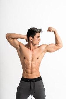 若い男が上向きの筋肉の上腕二頭筋を示す