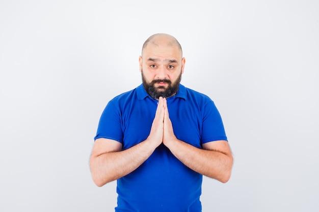 青いシャツの正面図でナマステジェスチャーを示す若い男。