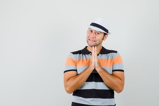 Молодой человек показывает жест намасте в полосатой футболке, шляпе и выглядит позитивно, вид спереди. место для текста