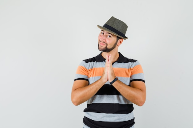 Young man showing namaste gesture in t-shirt, hat and looking grateful
