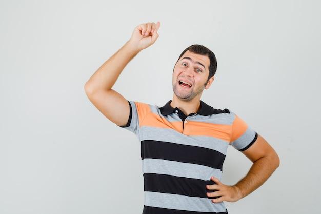 Tシャツを着て腰に手を置き、希望に満ちた表情で新しいアイデアのサインを示す若い男。正面図。