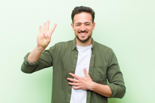 Молодой человек показывает номер четыре или четвертый с рукой вперед