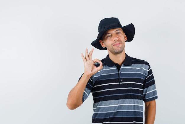 若い男はtシャツ、帽子で大丈夫なジェスチャーを示し、満足そうに見えます。正面図。