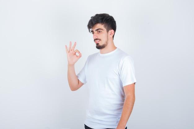 白いtシャツでokジェスチャーを示し、自信を持って見える若い男