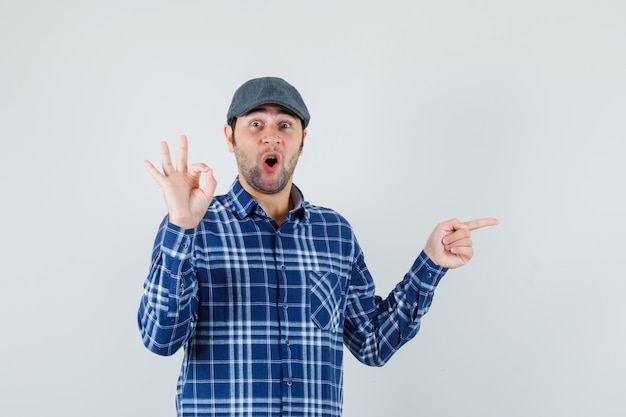 Giovane che mostra il gesto giusto, indicando da parte in camicia, berretto e guardando stupito. vista frontale.