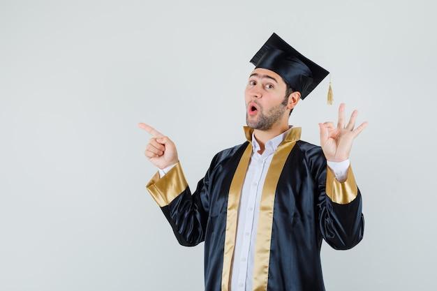 Giovane che mostra gesto giusto, rivolto verso l'alto in uniforme laureato e guardando stupito. vista frontale.