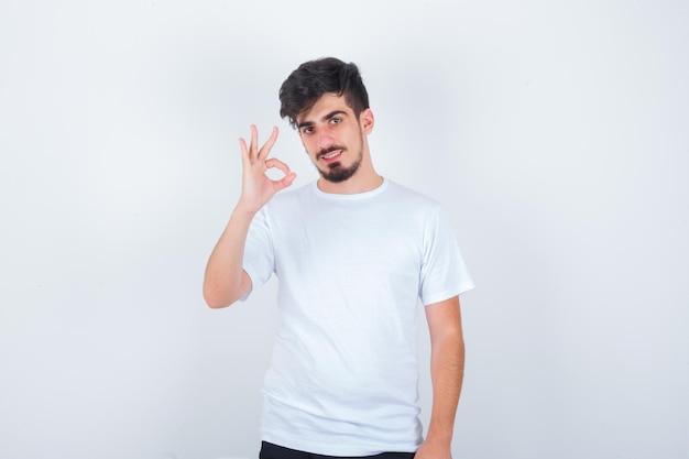 Giovane che mostra gesto ok in maglietta bianca e sembra sicuro