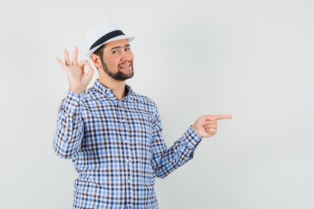 Okのサインを示し、チェックのシャツ、帽子、陽気に見える側を指している若い男